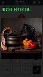 На плите поставлен котелок, где уже лежат помидоры и стоит кувшин