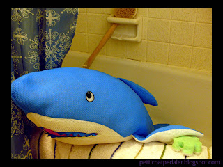 Photo of a blue plushie shark in a bathtub with a towel and sponge.  Black border around the photo.