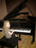 little girl on bench in front of grand piano