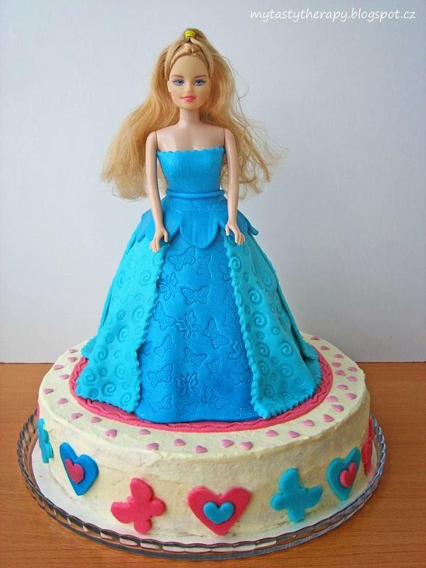 kulatý krémový dort zdobený marcipánovými srdíčky a motýlky, na kterém stojí princezna v modrých šatech, které jsou také z dortu potaženého mléčnou modelovací hmotou