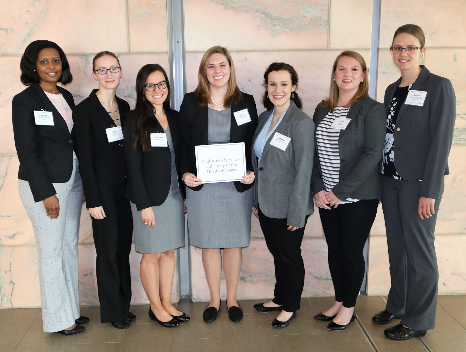 seven girls stand with a certificate
