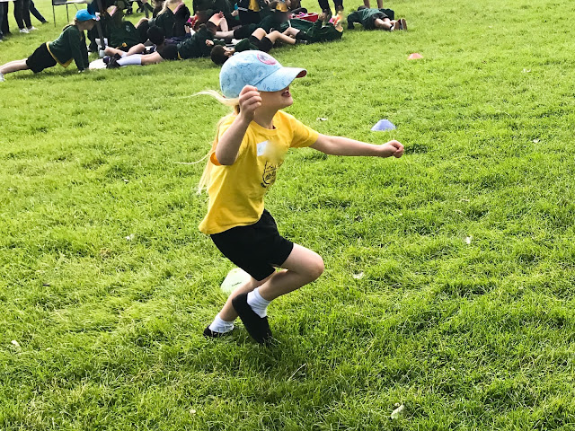 A young girl is running a race in school sports day, her hat is pulled so far down on her head she can hardly see where she is going.