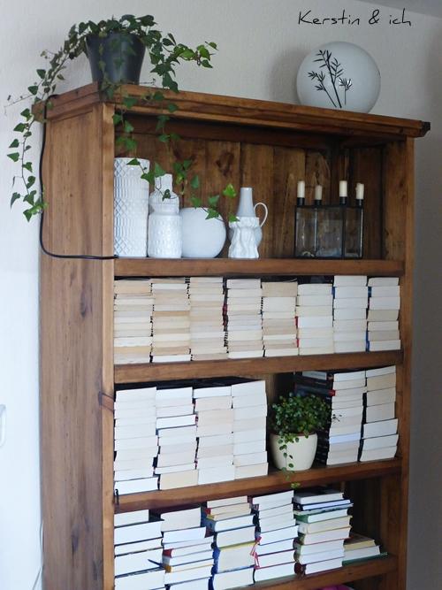 Bücherregal mit Pflanzen und weißer Vasensammlung