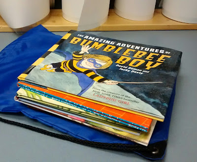Stack of books atop a blue drawstring bag on counter surface. Image and lettering visible on top book in stack identifies it as 'The Amazing Adventures of Bumblebee Boy' by David Soman and Jacky Davis. Behind the stack of books, four book-jacket laminate rolls are stood on end