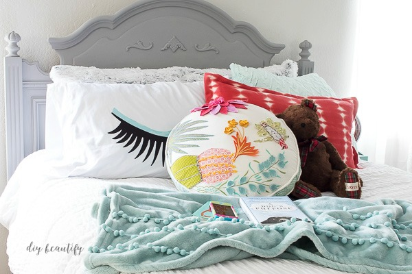 colorful pillows on neutral bed