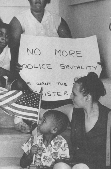 Anthony Quinn, five-years-old, holds an American Flag while sitting on the steps at the had Mississippi Governor's office. His mother holds a sign reading No more police brutality. 1965 Photo by Matt Herron