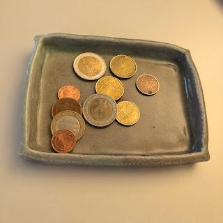 Münzen auf einem Keramikteller von Regine Hohmann