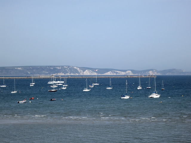 Portland Harbour, Dorset, with boats, Harbour Wall and Purbeck Cliffs beyond.