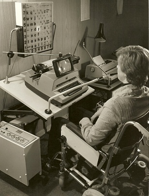 A young man in a wheelchair has a sip-puff tube in his mouth, looking at an illuminated alphabet and command board in front of him (via light-bulbs). A type-writer with magnifying glass sits between them.