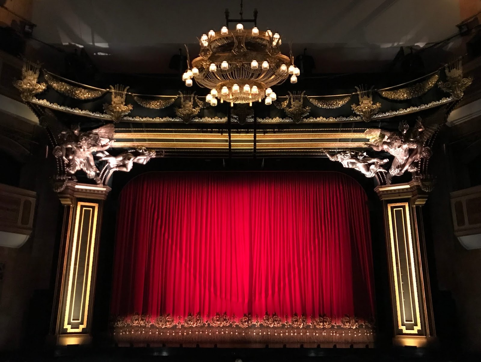 A photo of a theatre, with it's red curtains drawn, two squared coloumns either side with carved figures at the top, and a chandelier hanging from the ceiling at the top of the photo.