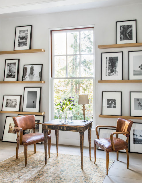 Leather arm chairs in modern farmhouse with wood ledges and art by Giannetti Home