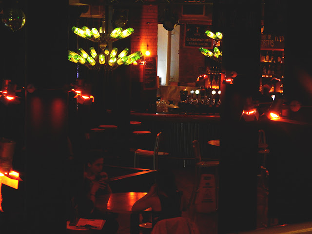 A dark bar lite by bottles and orange lights