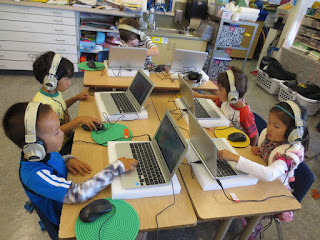 Students sit at computers doing work with headphones on