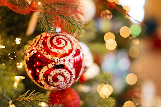 A close-up of a metallic red bauble with swirling white patterns, hanging on a Christmas tree. Other decorations and lights are out of focus in the background.