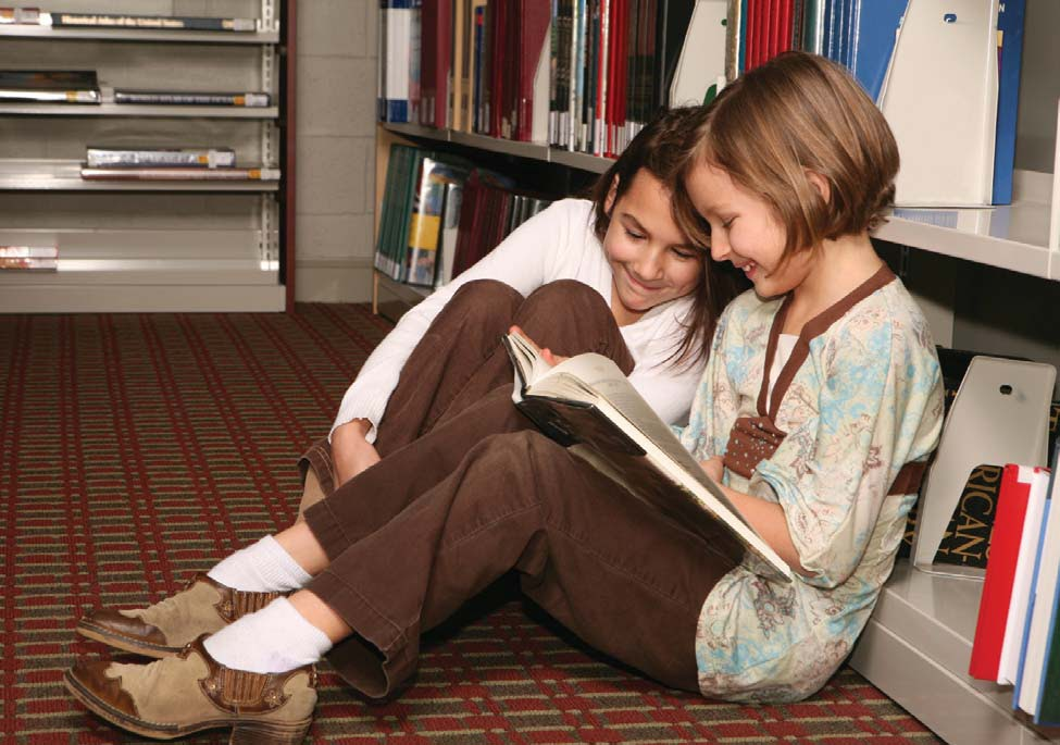 NAMC Montessori teachers first week of successful elementary school year girls reading book in library together