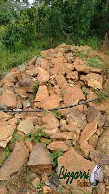 Pedra para revestimento, do tipo pedra moledo, com tamanhos diversos, nesse tom meio avermelhado com a espessura entre 10 cm a 18 cm.