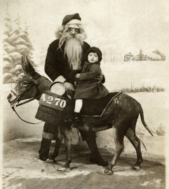 Old photo of Santa posing with a little girl riding a donkey. Santa looks very creepy. c.1930s. A Pleasant Christmas Story and other stories of Christmas Creepers. marchmatron.com