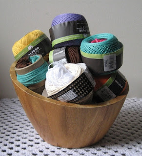 A wooden bowl has a collection of coloured skeins of 4-ply cotton.