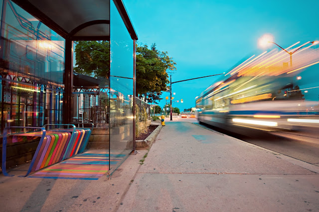 Photo of a bus stop with a vehicle passing by