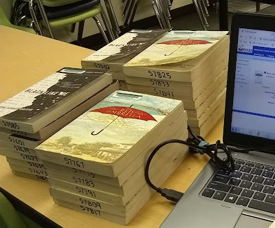 Four stacks of books consisting of two separate titles, 'Black Like Me' and 'The Red Umbrella.' Each title is grouped into two stacks each, out of the total four. The stacks of books are next to a laptop computer. The books each have a barcode in the upper-left corner, front cover. Numbers have also been written in black pen across the books' pages, bottom-edge