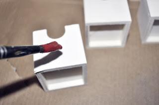 pincel con pintura roja apunto de posarse en la primera caja