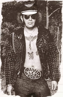 old photo of David Allan Coe wearing leather jacket and big belt buckle