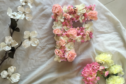 a wooden letter 'f' filled with white, pink, and coral artificial flowers, laying on a white sheet, and surrounded by leftover artificial flowers