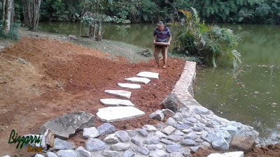 Bizzarri fazendo a execução do caminho de pedra em volta do lago com junta de grama sendo a pedra cacão de São Tomé. 27 de fevereiro de 2017.