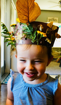 child wearing crown made from construction paper and nature items