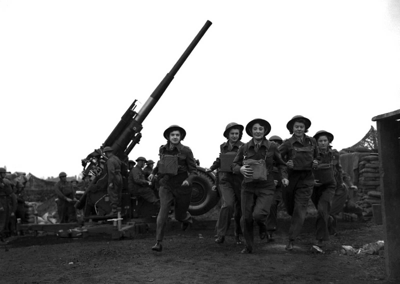 Ack-Ack Girls, members of the Auxiliary Territorial Service (ATS), run to action at an anti-aircraft gun emplacement in the London area on May 20, 1941 when the alarm is sounded.
