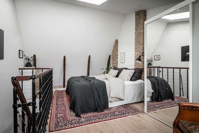 Dormitorio en la buhardilla con armario de puerta de espejo y alfombra étnica