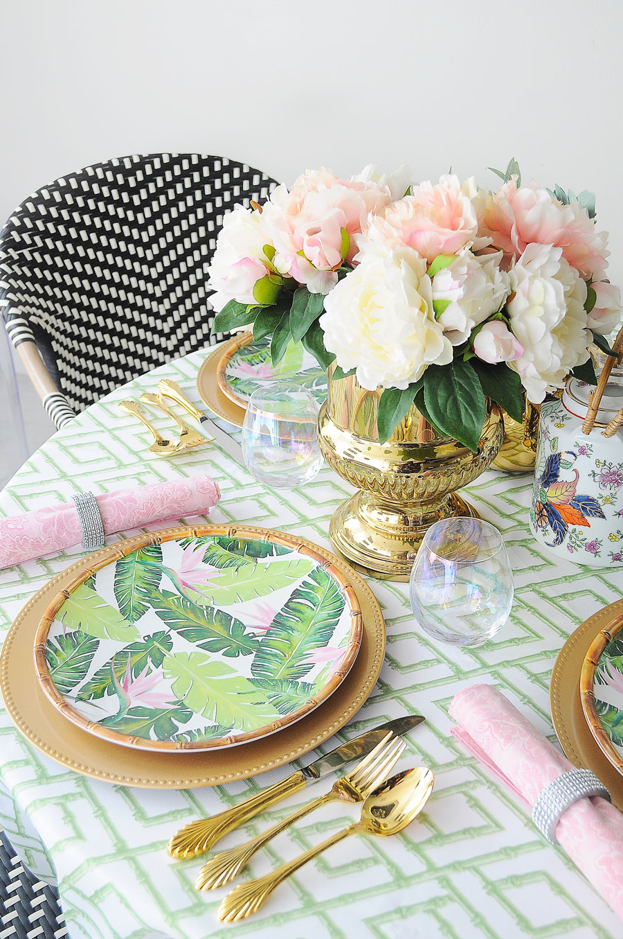 A small dining space centerpiece with major chinoiserie, Lilly Pulitzer and Palm Beach vibes. Featuring bamboo plates, gold chargers and flatware and pink peonies.