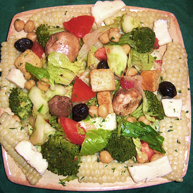 a plastic food dish to keep salad crisp. Inside this plastic dish is snap peas, grape tomatoes, sliced peppers, garbanazo beans, roasted beets, olives, shredded cabbage, broccoli, with homemade Italian dressing. In the backround of red skinned potatoes.