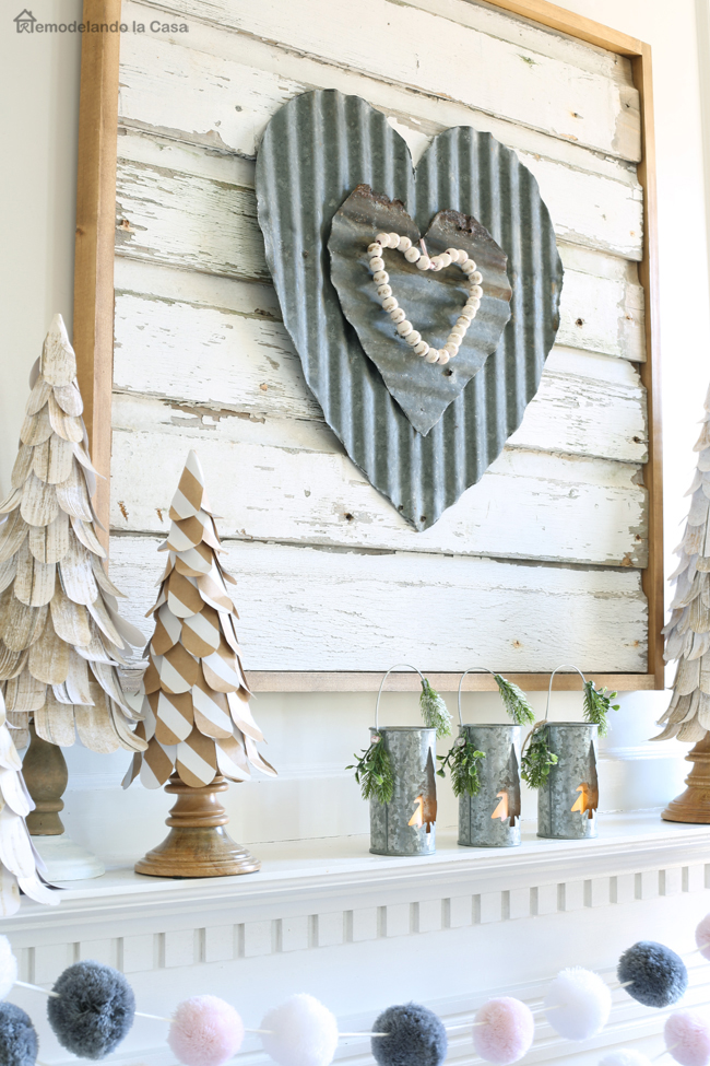 corrugated metal heart wall art and paper cone tree on mantel display