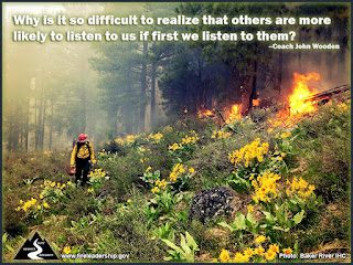 Why is it so difficult to realize that others are more likely to listen to us if first we listen to them? – Coach John Wooden (Wildland firefighter with drip torch on a flowery slope with downed, burning trees and smoke)