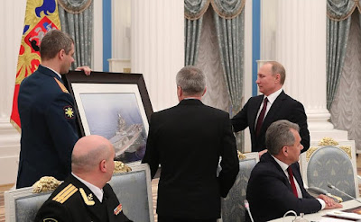 Vladimir Putin watching the picture of Admiral Kuzcenov.