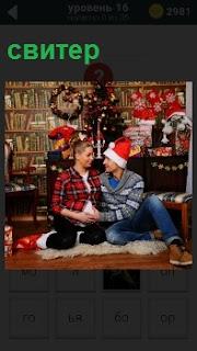 Женщина и мужчина сидят на полу, мужчина одет в свитер и шапочку Деда Мороза