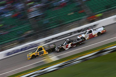 Grant Enfinger leads Kyle Busch and Brett Moffitt during the NASCAR Camping World Truck Series 37 Kind Days 250