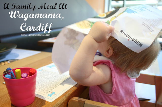 A family meal at Wagamama Cardiff - header photo of baby sat in high chair with Wagamama menu on her head