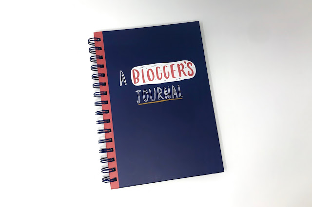 """A navy ring bound book with the writing """"a blogger's journal"""" on it"""
