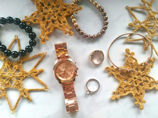 zdjęcie świąteczne zegarek z różowego złota, biżuteria i szydełkowe gwiazdki