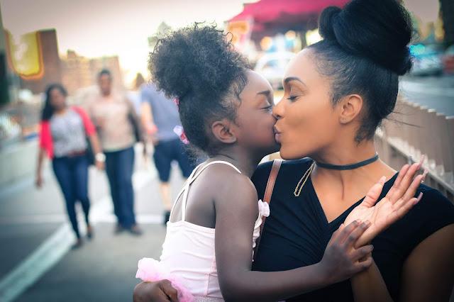 una madre de raza mixta afroamericana besando a su hija de raza negra