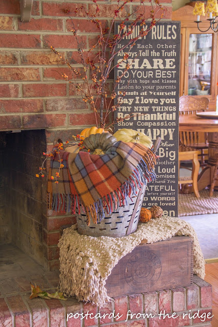 old wooden crate with metal olive basket and plaid throw blanket on brick fireplace hearth