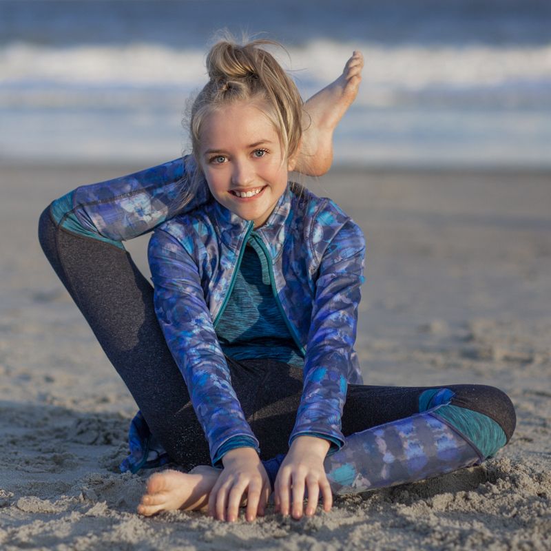 tween girl doing contortion yoga pose on the beach