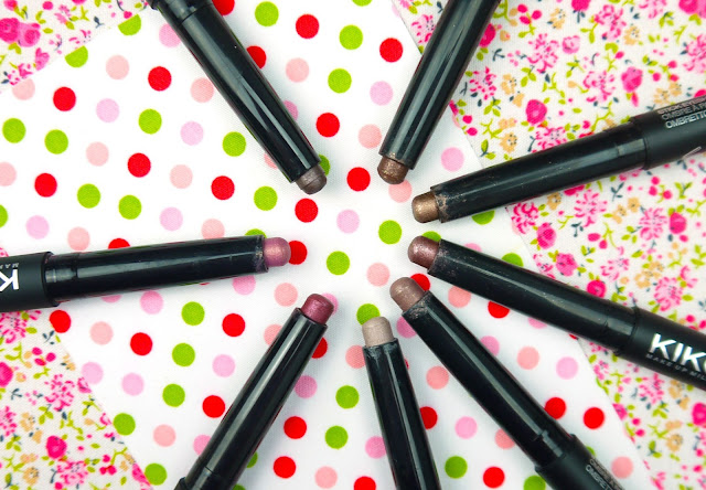 black eye crayons arranged in a circle on a red and green polka dot background