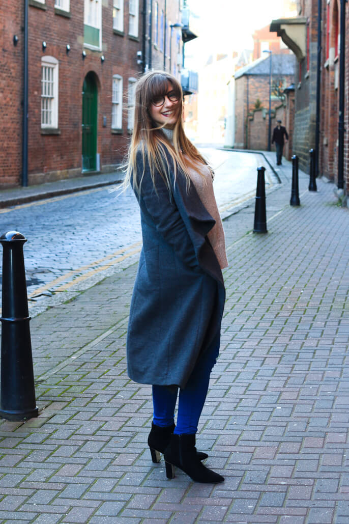 Winter fashion girl in long grey coat and jeans