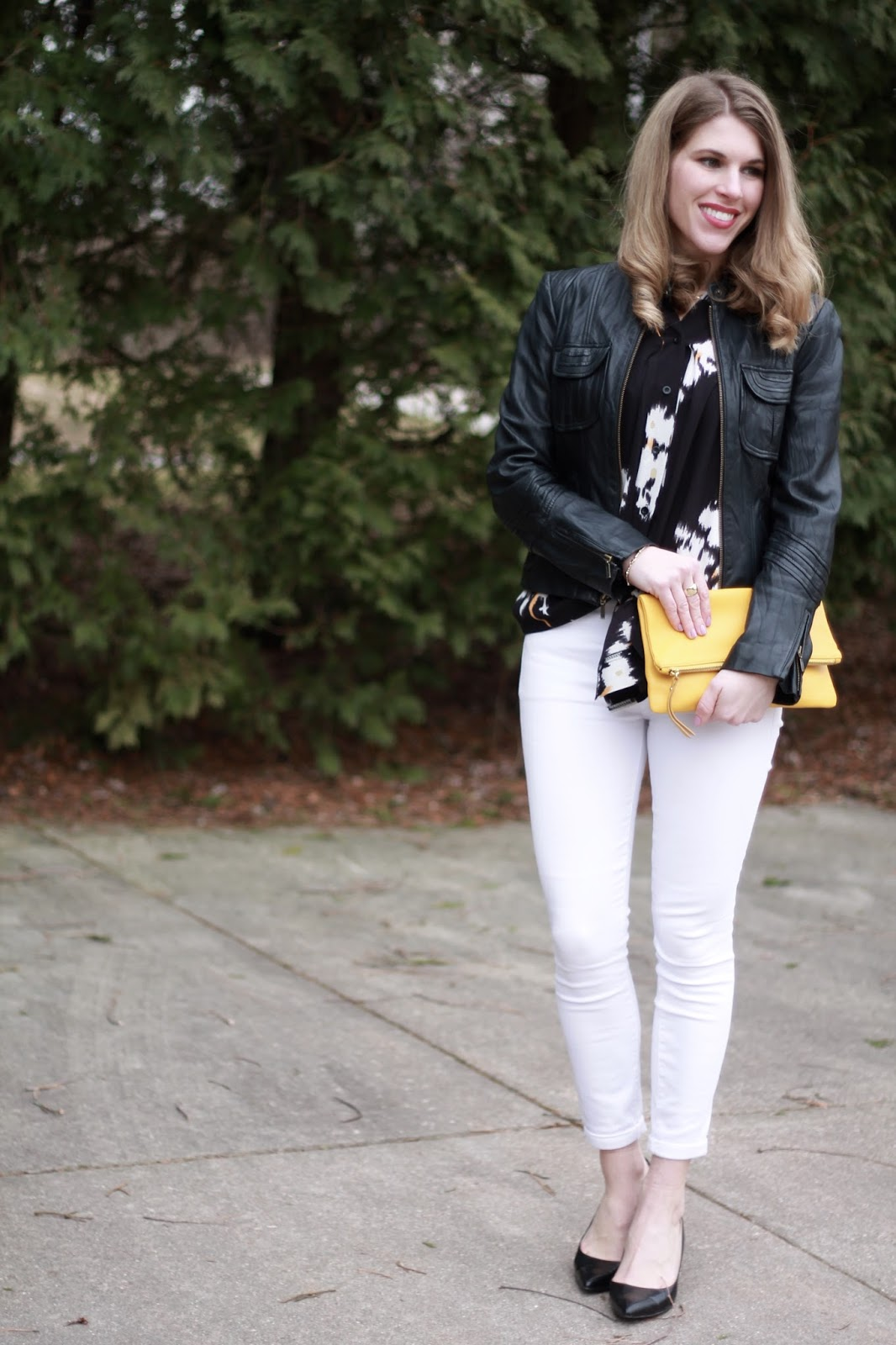 black floral tie top, black moto jacket, white jeans, black heels, yellow clutch
