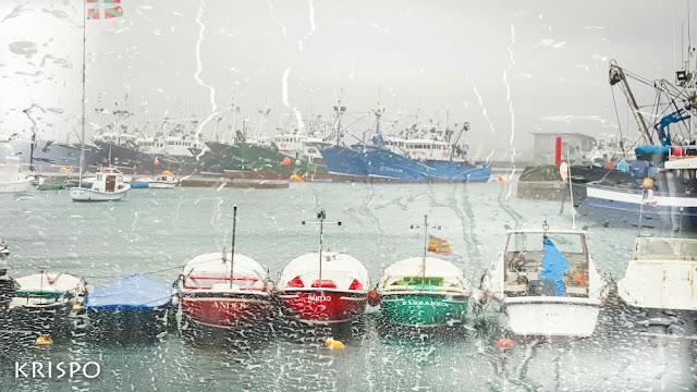 barcas y barcos en el puerto de hondarribia tras una ventana mojada con lluvia