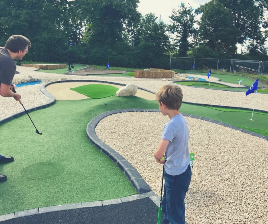 Hitting a golf ball over a small mound in adventure golf.