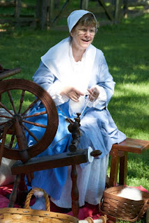 Woman wearing 17th-century style skirt and short gown with white kerchief and white cap. She is seated at a spinning wheel in an outdoor setting.